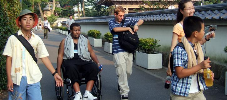 African-American wheelchair user strolling with his exchange group in Japan