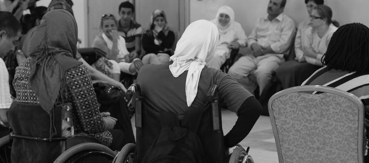 Black and white photo of people, including several women wheelchair users, sitting in a circle listening to a speaker.