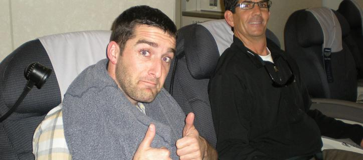 Exchange participant gives thumbs up from his airplane seat at the start of his journey