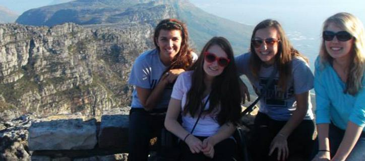 Shannon in front of mountain vista with three other young women