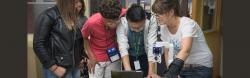 A teacher showing 3 international students a magnifier and iPad.