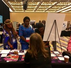 Three women wearing traditional African clothes stand at an info table in a large expo hall with another woman sitting behind table.