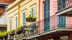 New Orleans buildings painted in pastel pinks and yellows with balconies adorned with plants