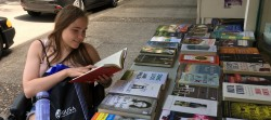 Student using a powerchair browsing books for sale on a table outside a shop