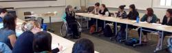 Susan Sygall, in wheelchair, at center of long tables of students