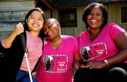 Three women wearing pink WILD logo t-shirts smile joyfully; one holds a white cane; one is seated in a wheelchair