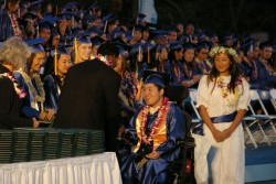 A young man, who uses a power wheelchair, wears his graduation regalia and crosses stage to receive diploma.