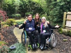 """Three people grouped together in a Japanese-style garden surrounded by bamboo. A brown man and white woman, both in their 50s or 60s, are seated in manual wheelchairs and make an """"om"""" gesture with their hands."""