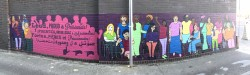 Panoramic shot of colorful mural depicting disabled women activists from many world cultures.
