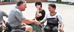 American man seated in a wheelchair extends his hand to two Chinese delegates.