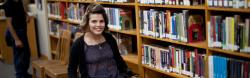 Ana smiling in front of bookshelves at school library