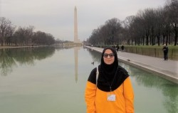 Asma wears a bright orange long sleeved salwar kameez and black headscarf, nametag on a lanyard around her neck, and sunglasses. Behind her is the Reflecting Pool, with the Washington Monument visible far in the distance. The sky is overcast.