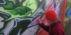 "A young man, viewed from behind, uses a purple marker to write ""Eric C"" on a colorful wall that has been airbrushed with green, black and pink patterns. He wears a knit cap and sweatshirt."