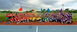 Panoramic photo of large group of students sitting on track.
