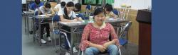 Ming sitting in wheelchair in front of classroom as students behind her have their heads down writing.