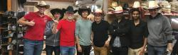 Ahmed standing with a large group of friends in a cowboy store all wearing cowboy hats.