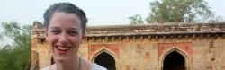 Volunteer to India smiles widely with arched entryways behind