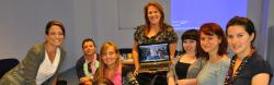 Team Macedonia of seven women gathered around laptop