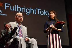 A man who uses a power wheelchair is speaking on a stage with a sign reading Fulbright Tokyo. A woman stands next to home holding a mic.
