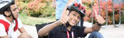 Muhammad gives two thumbs up as he gets set up on a recumbent bicycle.
