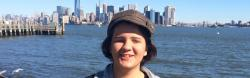 Pinar smiling in front of the New York City skyline