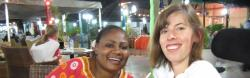 Rachel and a Tanzanian friend enjoy a meal in a courtyard.