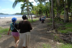 Two young women walk together along a jungle path parallel to a beach. One woman is carrying a white cane.