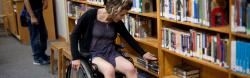 Wheelchair user searches shelves of publications