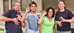 """Four people standing outdoors smile at camera while displaying ASL signs on their hands. An older white man and woman make sign for """"interpreter"""" while two younger people of color show their name signs."""