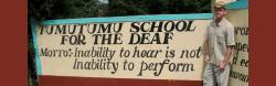 "A man stands next to a hand-painted sign that reads ""Tumutumu School for the Deaf, Motto: Inability to hear is not inability to perform"""