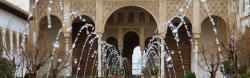 water fountain spouting with alhambra in background