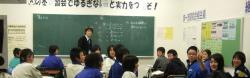 View of a Japanese classroom through a window; a teacher at a chalkboard