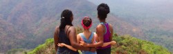 Three young women with their backs to the camera face a view overlooking a valley far below.