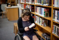 A girl in library looks down at a book in her lap