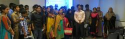About two dozen Bangladeshi men and women stand in a room before a projector screen