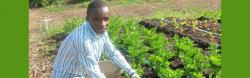 Tijani, a young boy, kneeling in a garden plot