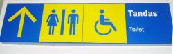 """Blue and yellow sign indicating lavatory. Text reads """"Tandas - Toilet"""""""