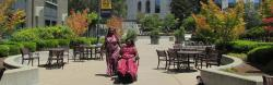 Two African women, one a power wheelchair user, in a courtyard.