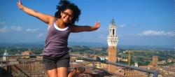 A girl smiles in mid-year at a point overlooking a city in Italy.