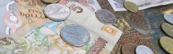 An assortment of foreign currencies are scattered on a table.