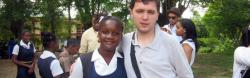 A young American man with autism poses with a Jamaican school girl.