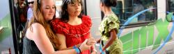 A young Latin American blind woman exits a public bus as a sighted American woman guides her.