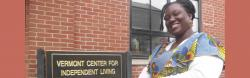 "A smiling Ghanaian woman is near a building and sign that reads ""Vermont Center for Independent Living."""