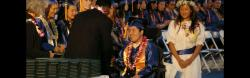 An international student from Asia in a power wheelchair wears a graduation cap and gown as he accepts his diploma.