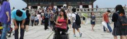 A young American woman in a power wheelchair in a busy square in an Asian city.