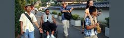 African American man in a manual wheelchair strolls along with others in Japan