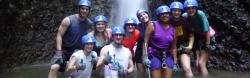 Study Abroad students including one who is blind pose with their hard hats on at the bottom of a waterfall in Costa Rica they ziplined by.