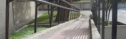 Low slope ramp with double handrails and tactile surface