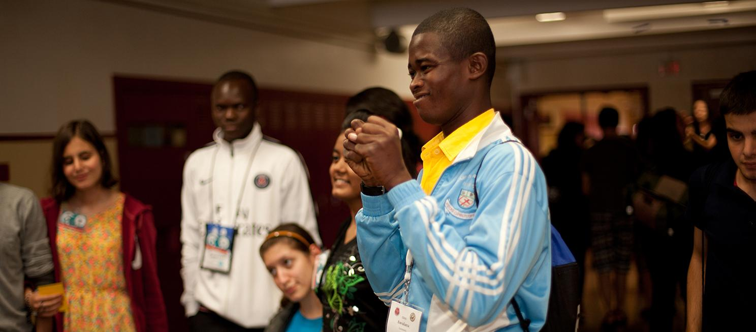 National Clearinghouse on Disability & Exchange. Increasing participation of people with disabilities in every international exchange program, everywhere.  Image: A young African man using sign language as other international youth look on.