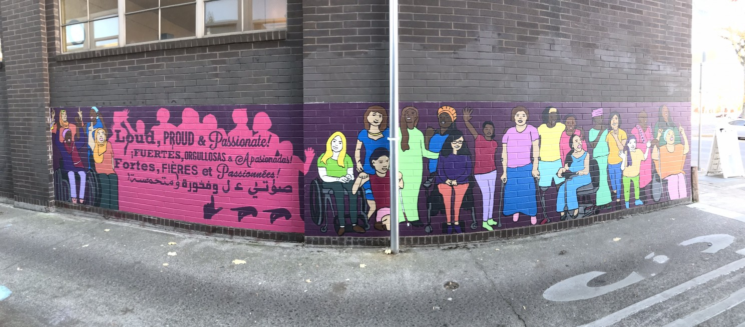 Panoramic shot of a colorful outdoor mural depicting disabled women activists of various world cultures